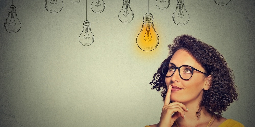 Thinking woman in glasses looking up with light idea bulb above head isolated on gray wall background-670262-edited.jpeg